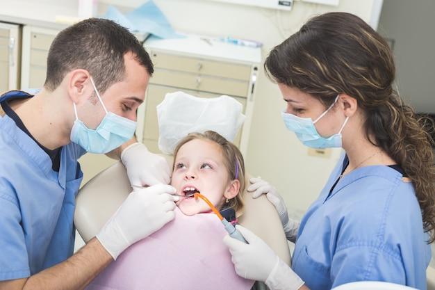 歯科医と歯科助手の若い女の子の歯を調べる