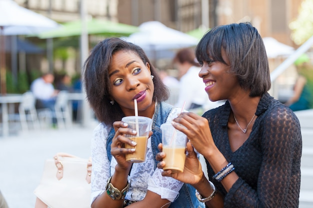 Две красивые темнокожие женщины наслаждаются освежающими напитками в нью-йорке
