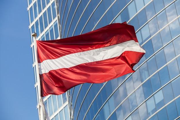 Латвийский флаг против небоскреба в риге