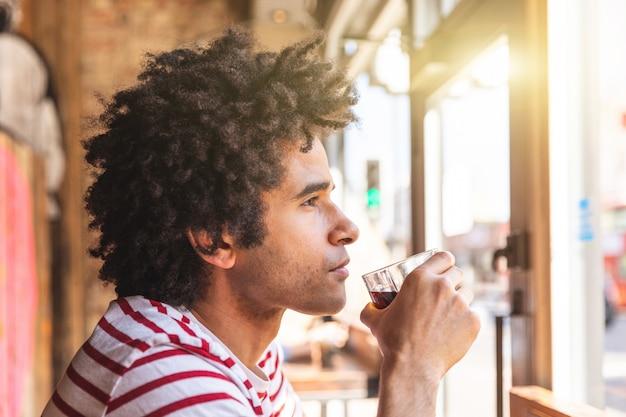 Вдумчивый человек смешанной расы, питьевая сода в кафе-баре