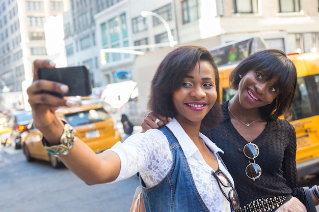 Две красивые темнокожие женщины, делающие селфи в нью-йорке