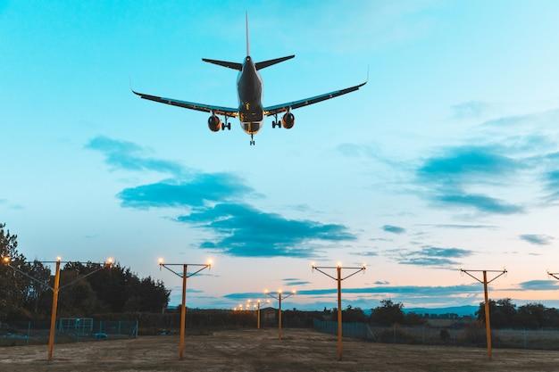 空港の夕暮れ時に着陸する飛行機のシルエット