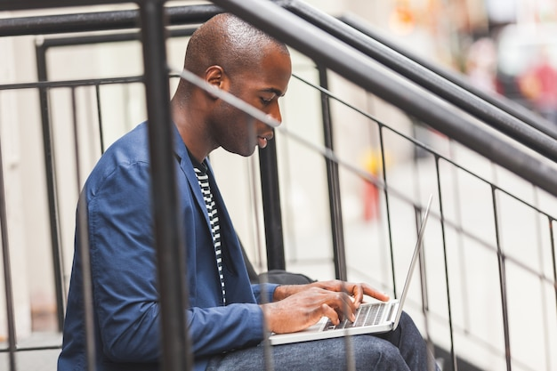 ニューヨークでノートブックを使用しているブラックガイ