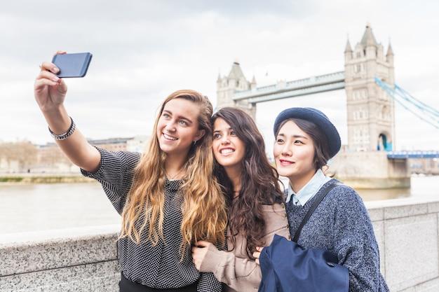 Многорасовая группа девушек, делающих селфи в лондоне