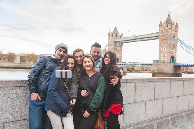 Группа друзей, наслаждаясь принимая селфи в лондоне
