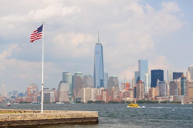 背景にニューヨークの高層ビルとアメリカ合衆国の国旗