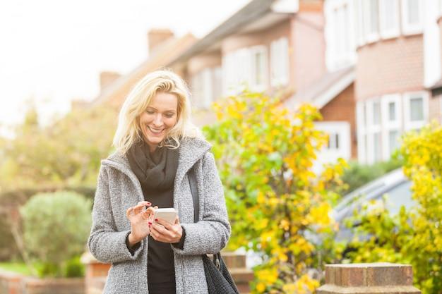 ロンドンの住宅街でスマートフォンを見ている女性