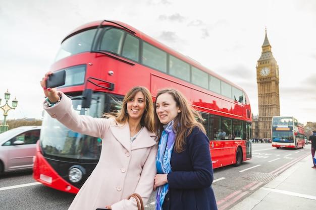 Женщины туристы, делающие селфи в биг бен в лондоне