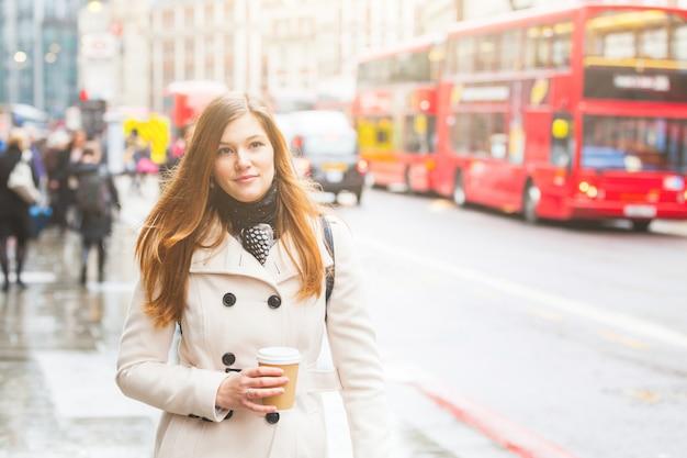 ロンドン、道路に沿って歩く若いビジネス女性