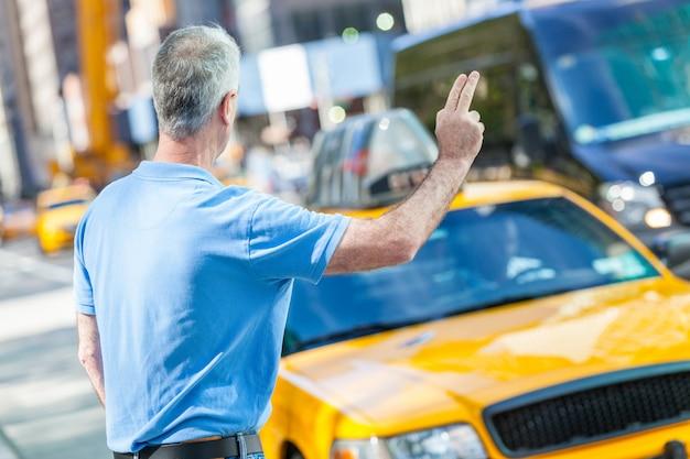 Старший мужчина вызывает такси в нью-йорке