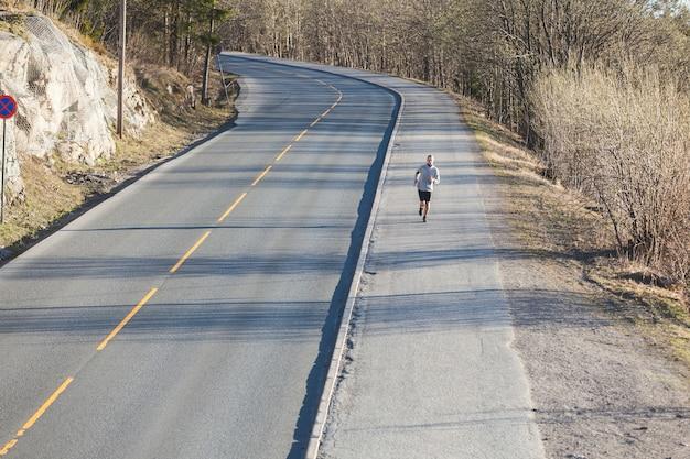 空の山道に沿って外を走っている若い男