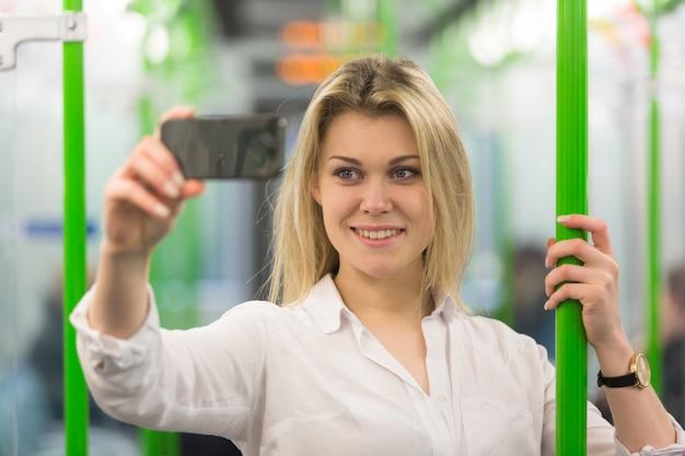 Молодая женщина, принимая селфи в лондонском поезде