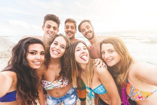 Многорасовая группа друзей, принимающих селфи на пляже