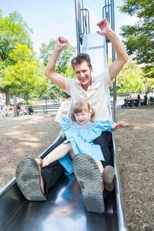 Отец и дочь играют на горке в парке