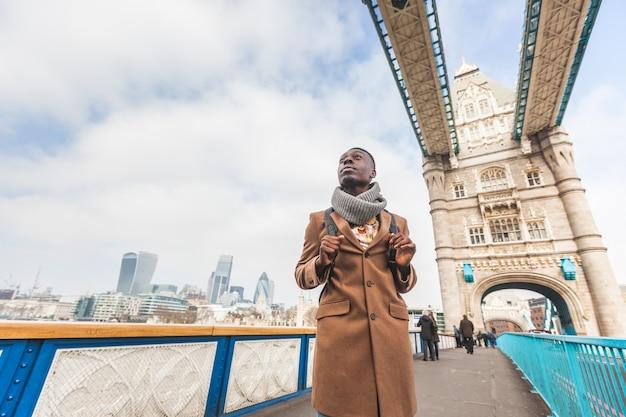 ロンドンのタワーブリッジの若い黒人男性