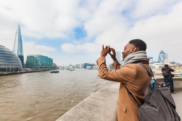 彼のスマートフォンとロンドンで写真を撮る男