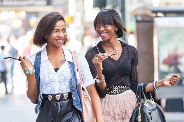 Две красивые чернокожие женщины гуляют в нью-йорке