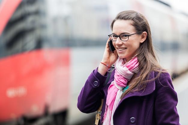 駅で携帯電話で話している若い女性