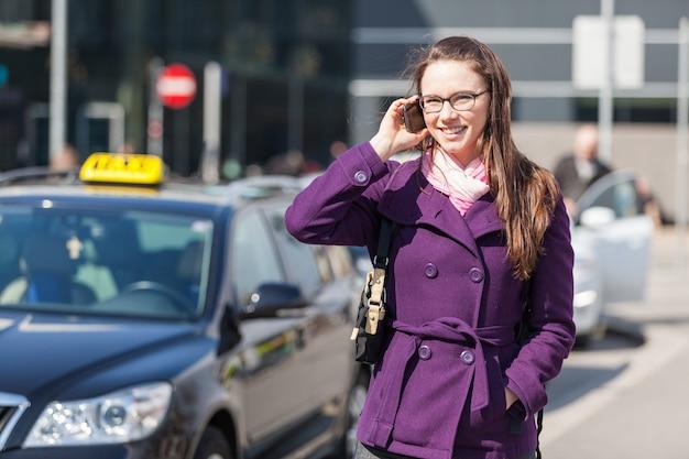タクシーを待っている携帯電話で話している若い女性