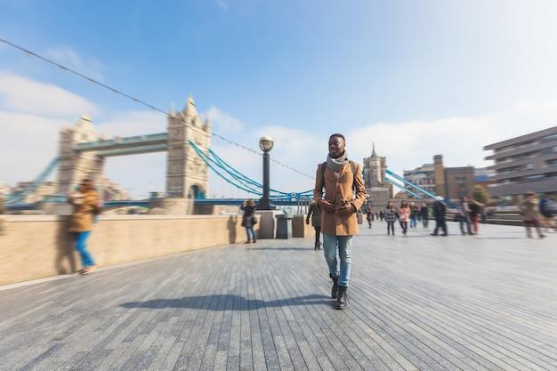 テムズ川の歩道でロンドンを歩く男
