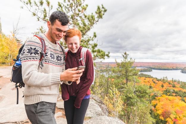 カラフルな秋のシーズン中にオンタリオ州でのハイキングをカップルします。