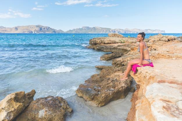マヨルカ島の岩の上に座っている海辺の女