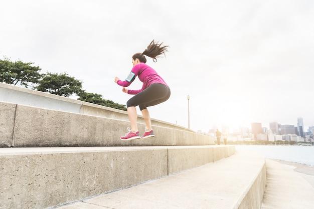 シカゴのスカイラインと足の運動を行う若い女性