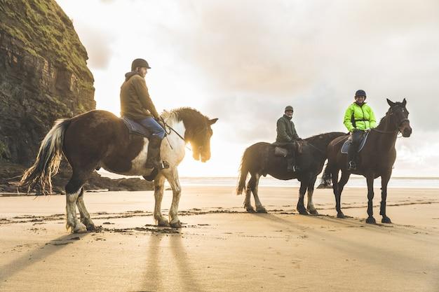 曇りの日にビーチで馬を持つ人々