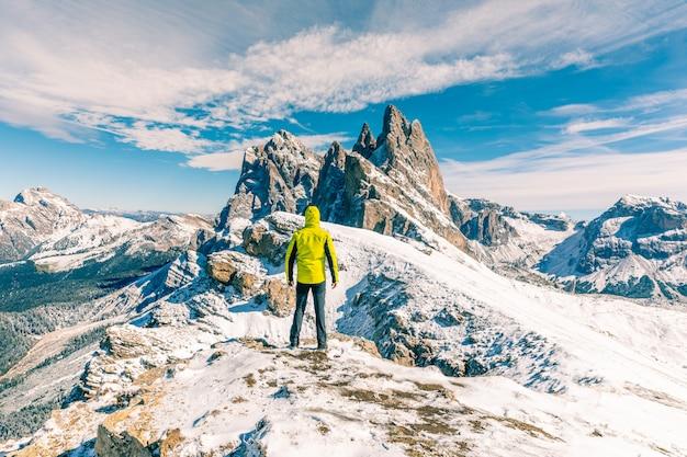 雪に覆われた山の頂上に立っている人