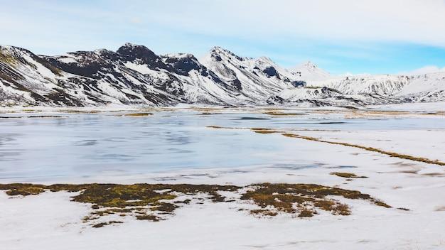 Зимний пейзаж в исландии, замерзшее озеро и горы