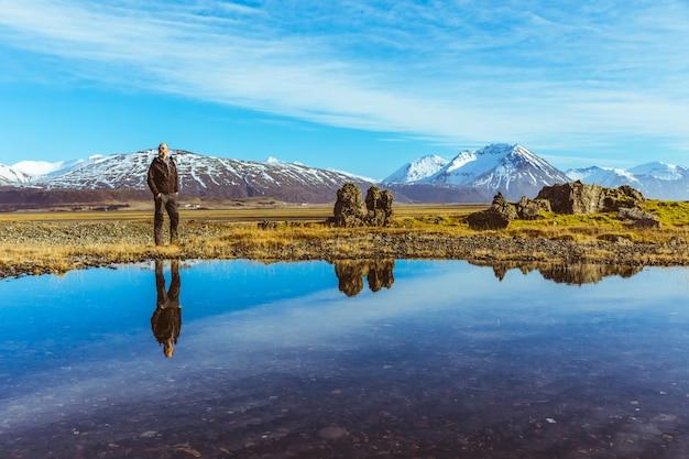 Человек исследователь в исландии с его отражением на воде