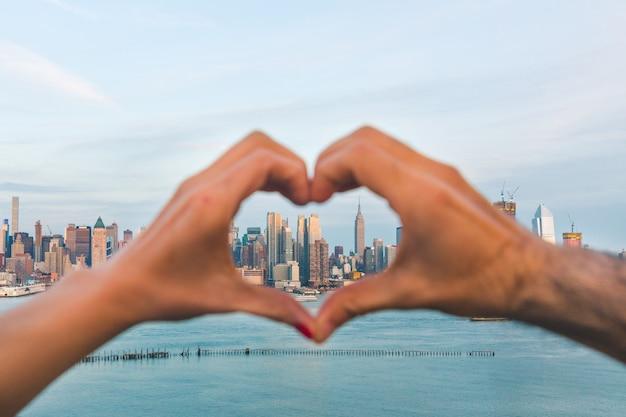 ハート型のニューヨークのスカイラインと手