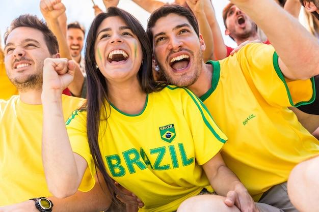 Бразильские болельщики празднуют на стадионе с флагами