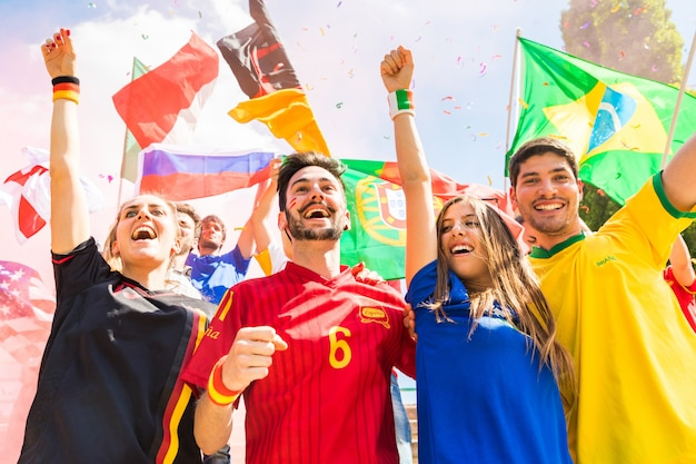 スタジアムで一緒にさまざまな国からの幸せなファンサポーター