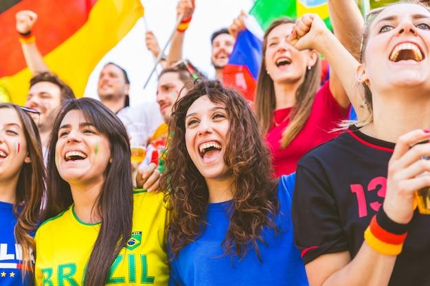 Счастливые болельщики болельщиков из разных стран вместе на стадионе