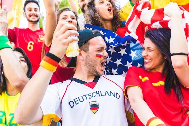 Международная пара болельщиков празднует вместе на стадионе во время матча