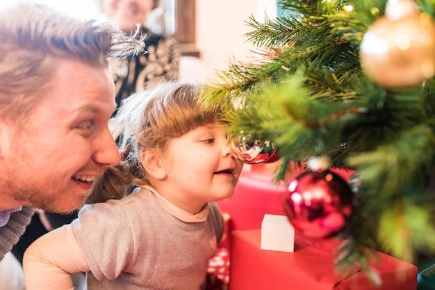 女の赤ちゃんとパパのクリスマスツリーの飾りで遊ぶ