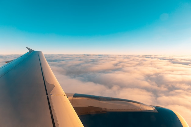 窓から雲の上の飛行機の翼ビュー