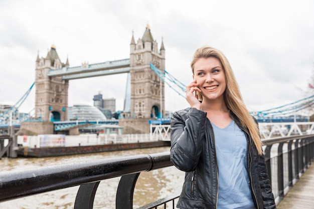 ロンドンのタワーブリッジの近くで電話で話している女性