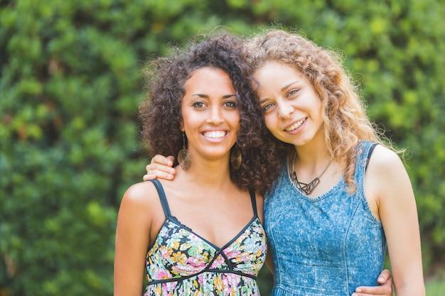 公園で多民族の幸せな若い女性の肖像画