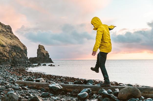 スコットランドの海辺でログ上のバランスにぶら下がっている男