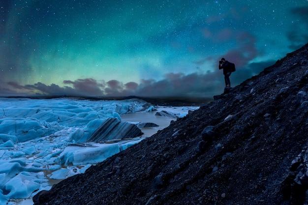 Фотограф фотографирует ледник и северное сияние в исландии