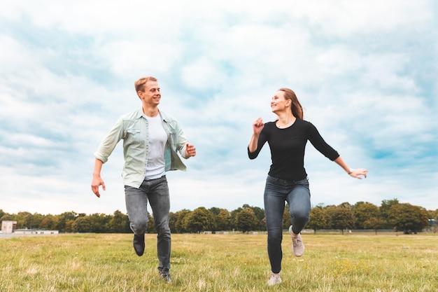 幸せなカップルを実行し、テンペルホーフ公園で一緒に楽しんで