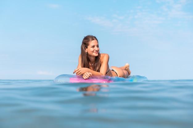 膨脹可能なマットレスでリラックスした海辺で美しい少女
