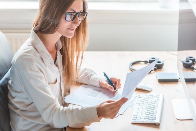 Бухгалтер пишет на бумаге у себя дома офисный стол