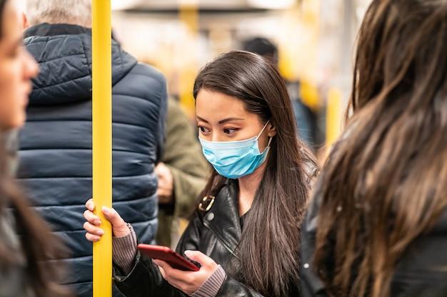 電車の中で顔のマスクを着ている中国の女性