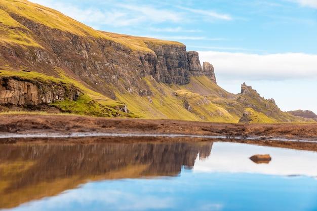 晴れた日にスコットランドのスカイ島の美しい旅行風景-日当たりの良い夏の日に水の池にウラプール山の崖のカラフルな反射-自然と旅行の概念