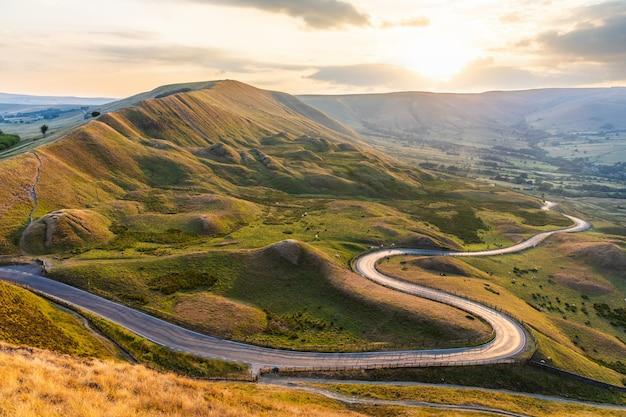 Красивая извилистая дорога и холмы на закате в пик дистрикт - пейзажный вид с золотым светом в великобритании - природа и концепции путешествий,