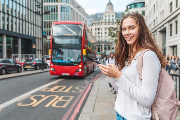 ロンドンのバス停でスマートフォンを持つ女性の笑顔-彼女の電話を使用してロンドンの一日のバスの時刻表をチェックする笑顔の少女の肖像画-ライフスタイルと交通機関の概念