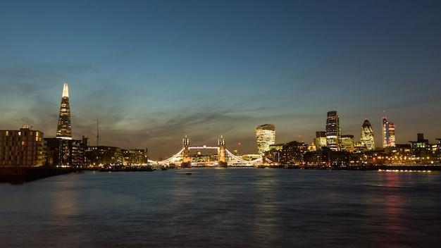 前景にテムズ川と夕暮れ時にロンドンのスカイライン